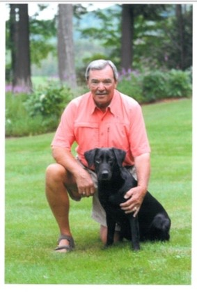 Photo of John Russell and his black Labrador Retriever
